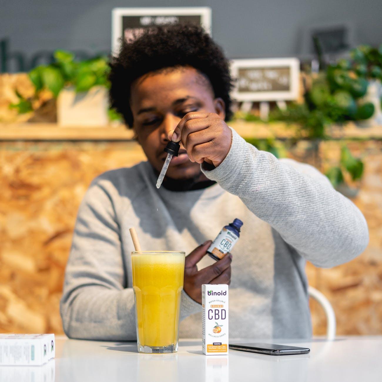 homme ajoute huile de cbd jus d'orange